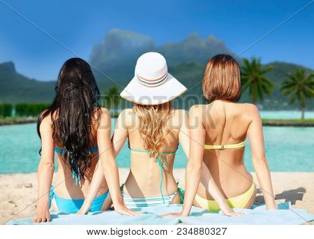 summer holidays, vacation, travel and people concept - group of women in swimwear sunbathing over bora bora island beach background