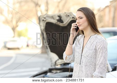 Serious Driver With A Broken Down Car Calling Insurance On Phone On The Street
