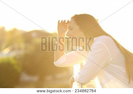 Side View Portrait Of A Happy Woman Scouting With The Hand In Forehead In A Balcony At Home At Sunse