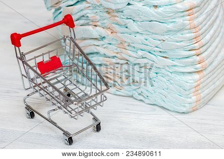 Stack Of Diapers Or Nappies And Mini Shopping Cart, Parenthood And Money Concept