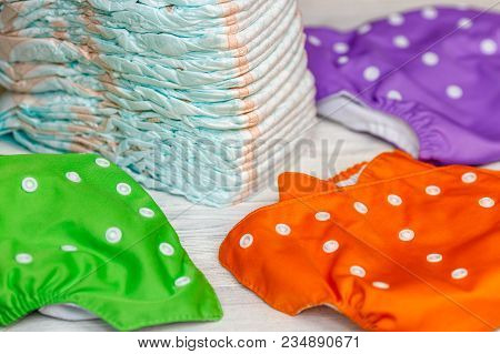 Stack Of Disposable Diapers Or Nappies And Colorful Reusable, Parenthood Concept