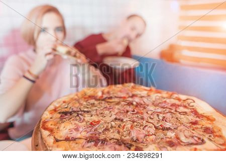A Delicious Pizza On The Background Of A Young Couple. A Couple Eating A Pizza In A Cafe. Pizza Is I