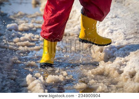Kid Legs In Yellow Rainboots Running In The Ice Puddle With Melting Snow At Sunny Spring Day, Outdoo