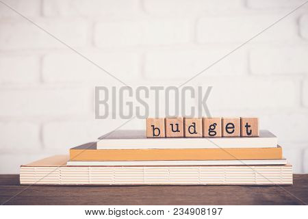The Word Budget, Alphabet On Wooden Rubber Stamps On Top Of Books And Table. Bricks Background, Blan