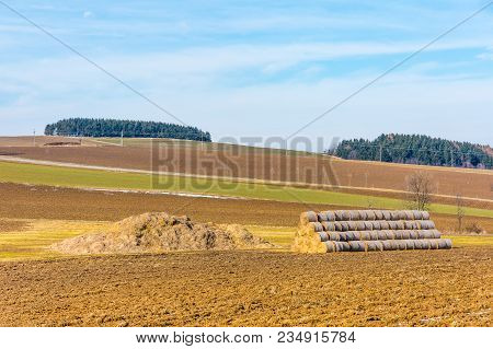 Straw Bales And Manure On The Countryside Field. Spring Fields And Preparation For Agriculture. Typi