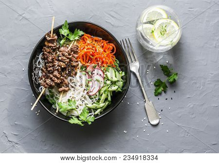 Rainbow Power Buddha Bowl. Asian Style Beef Skewers, Rice Vermicelli, Pickled Vegetables Salad Carro