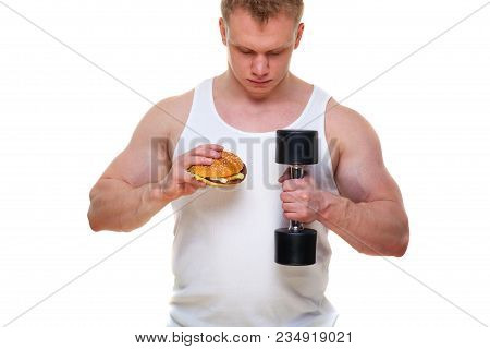 Fat Man With A Hamburger Holds Dumbbells Isolated On White. The Concept Of Choosing Between Harmful