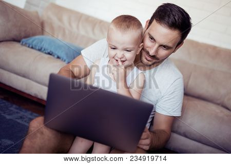 Father And Son Watch Cartoons On The Laptop