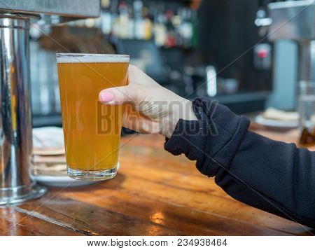 Woman Lifting Up Pint Glass Of Ipa Beer In A Bar In A Brewery