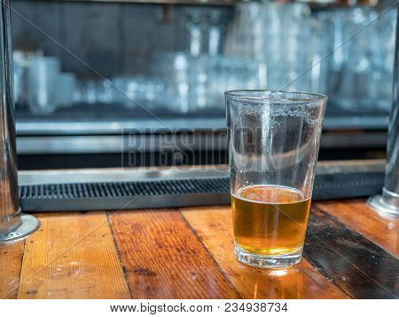 Almost Empty Pint Glass Of Beer Sitting On Woodencountertop For Last Call. Bar In Background