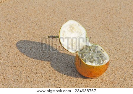 One Orange Open Passion Fruit With Seeds. Passion Fruit Closeup On The Beach, On The Sand And On The