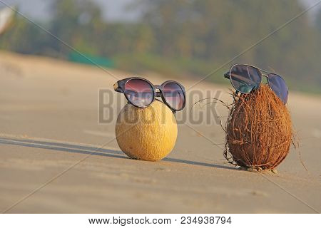 Orange Cut Melon With Seeds Inside And A Brown Coconut With Sunglasses, On The Beach And On The Sea,