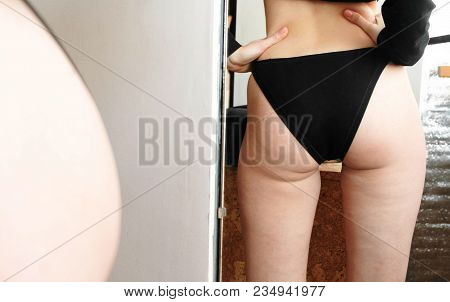 Cellulite In Women Booty And Legs. Closeup Ass Women In Front Of The Mirror In The Blue Trunks.
