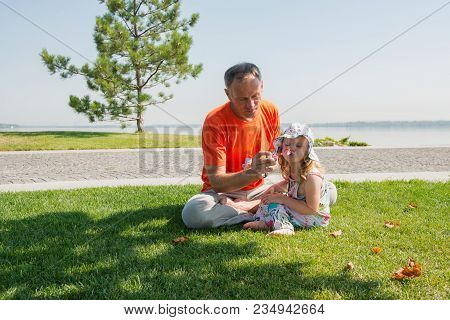 Attentive Father And His Small Enthusiastic Daughter Are Blowing Bubbles