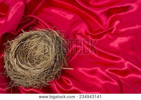 Empty Bird's Nest On A Beautiful Red Satin Background.