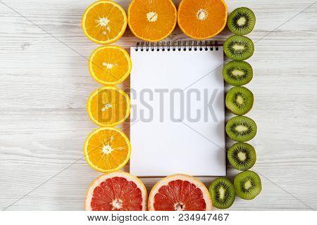 Top View Flat Lay Notebook With Sliced Kiwi, Orange, Grapefruit And Mandarin On Light Background. Su