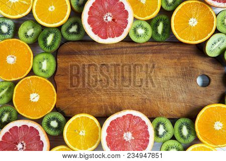 Flat Lay Top View Wooden Board With Sliced Kiwi, Orange, Grapefruit And Mandarin On Light Background