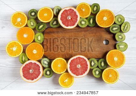 Flat Lay. Top View. Wooden Board In The Center With Sliced Kiwi, Orange, Grapefruit And Mandarin On