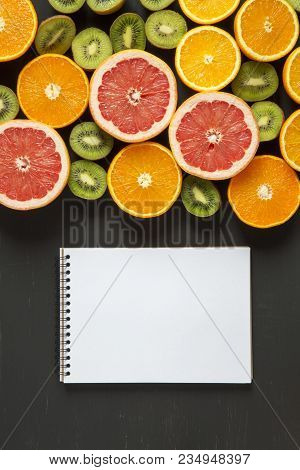 Flat Lay. Top View. Notebook With Sliced Colorful  Fresh Fruits: Kiwi, Orange, Grapefruit And Mandar