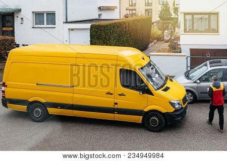 Paris, France - Mar 30, 2018: Courier Enters Dhl Yellow Delivery Van After Delivering The On Time De