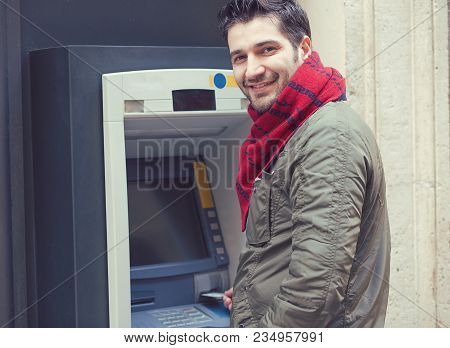 Handsome Confident Man In Outwear Inserting Plastic Card Into Atm Machine And Smiling At Camera.