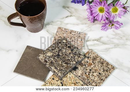 Granite countertop samples on white kitchen counter with coffee and flowers. Interior of a modern kitchen with natural granite countertop. granite texture on white marbled tile, closeup photo on granite tile surface on granite floor show granite tile text