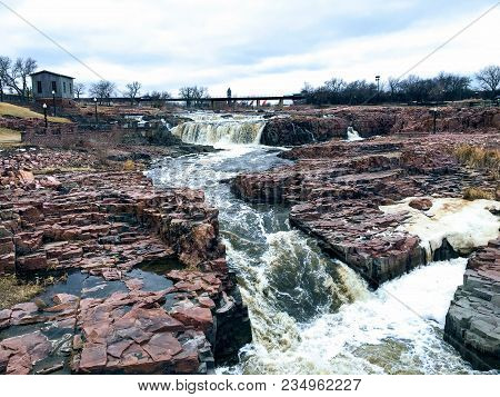 The Big Sioux River flows over rocks in Sioux Falls South Dakota with views of wildlife, ruins, park