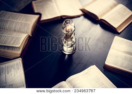 Closeup of holy bibles on the wooden table with candlelit