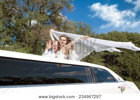 Bride And Groom Are Standing In Limo Waving