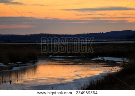 An Icy Sunset In Winter Time With A Semi Frozen River And Colorful Sunset In The Background.