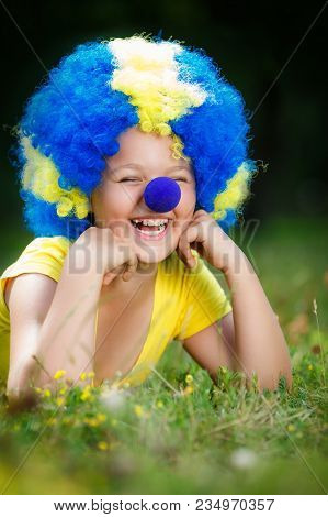 Smiling Girl In Clown Wig With Blue Nose Is Lying On The Green Grass In The Park