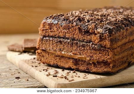 Chocolate Cake. Biscuit Dessert With Chocolate Powder With Chocolate Pieces On A Wooden Background