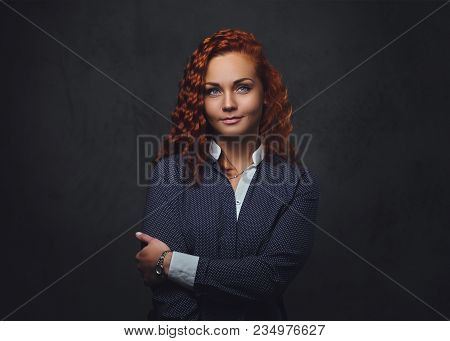 Redhead female supervisor dressed in an elegant suit over grey background. poster