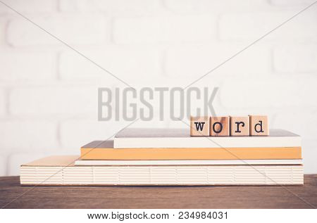 The Word Letters, Alphabet On Wooden Rubber Stamps On Top Of Books And Table. White Bricks Backgroun