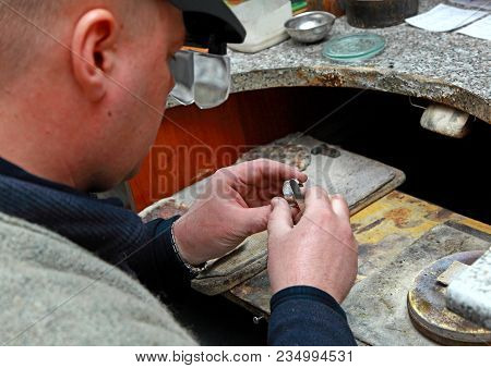 The Work Of A Jeweler. The Jeweller Sees A Silver Ring Through The Binoculars.