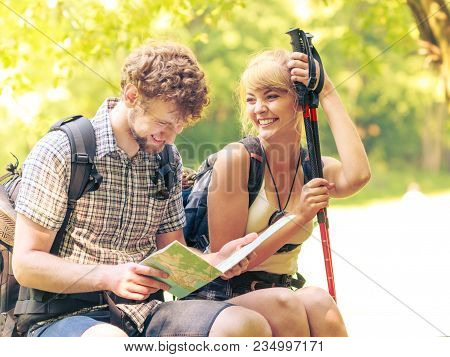 Man And Woman Tourists Backpackers Reading Map On Forest Trip While Resting. Couple Hikers Searching