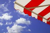 Red and white Awning over bright sunny blue sky poster