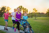 Beautiful, fit young family  jogging together outdoors along a paved sidewalk in a park pushing a stroller at sunset poster