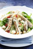 Chicken Caesar salad on blue. A healthy salad with romaine lettuce grilled chicken breast croutons bacon bits and dressing. poster