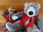 A grey teddy bear all dressed up for Christmas rests on a plaid runner accompanied by a star basket. The background is a log wall. poster