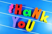 Thank you message with colorful letters against blue metallic board poster