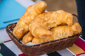 Fresh Croissants In A Basket On A Wooden Table.