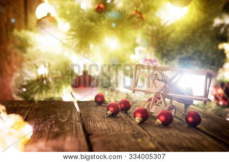 Christmas Holiday Background With Wooden Airplane And Christmas Red Balls On Wooden Table Top Over F