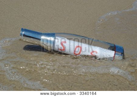 Message In A Bottle Lying In The Sand With Red Sos Signal Painted On A Piece Of Paper