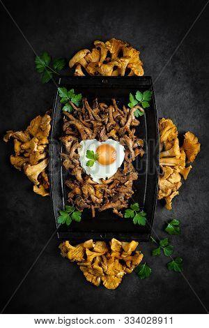 Sautéed Chanterelles Served With Fried Egg On A Black Cast Iron Plate
