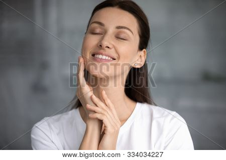 Smiling Attractive Young Woman Touching Hydrated Moisturized Healthy Facial Skin