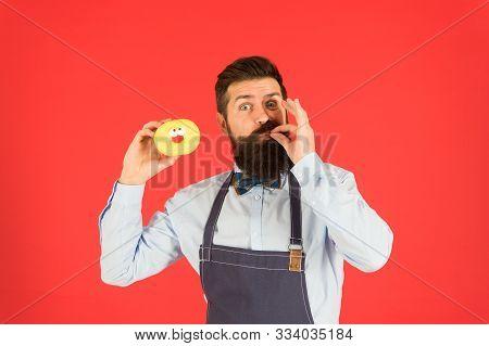 You Will Lick Your Fingers. Bearded Man Enjoying Sweet Taste Of Doughnut On Red Background. Baker Ea
