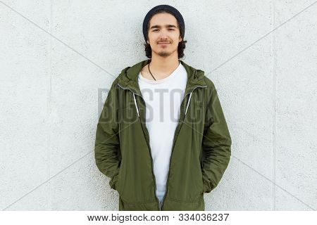Image Of Delighted Calm Youngster Standing Straight Outdoors, Having Pleasant Facial Expression. Smi