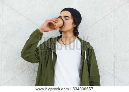 Outdoor Portrait Of Relaxed Youngster Drinking Hot Drink From Papercup Outdoors, Closing His Eyes, F