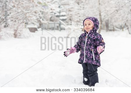 Happy Baby Girl Rejoices In Falling Snow, Moscow, Russia. Cute Little Child Having Fun Plays In Snow